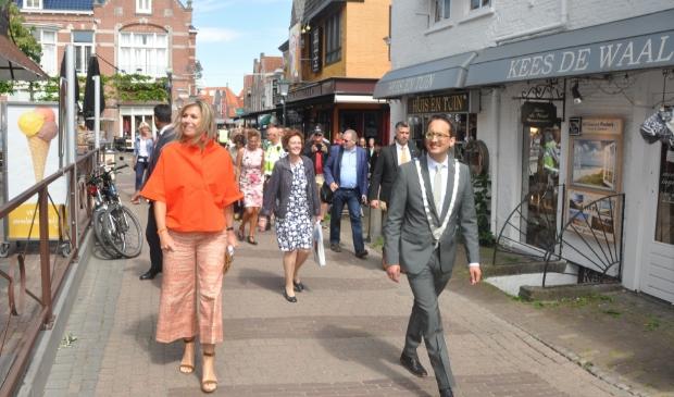 Koningin Maxima loopt begeleid door burgemeester Michiel Uitdehaag door Den Burg.