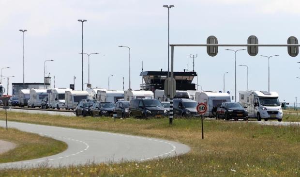 Verkeer dat van de boot komt, waaronder veel caravans en campers.