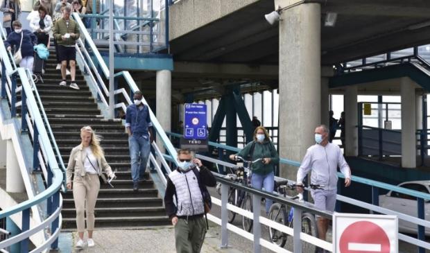 Reizigers die van de boot komen, zijn voorzien van mondkapjes.