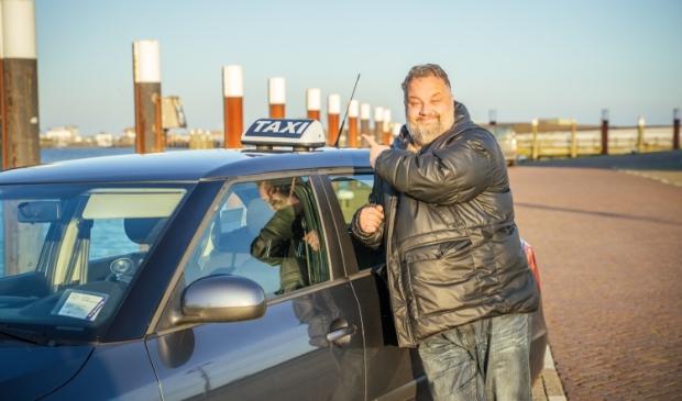 <p>Raymond Korf bij zijn taxi op de haven van Oudeschild.</p>