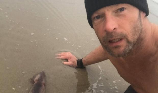 <p>Ruud van Holland met de pijlinktvis op het strand bij paal 28.</p>