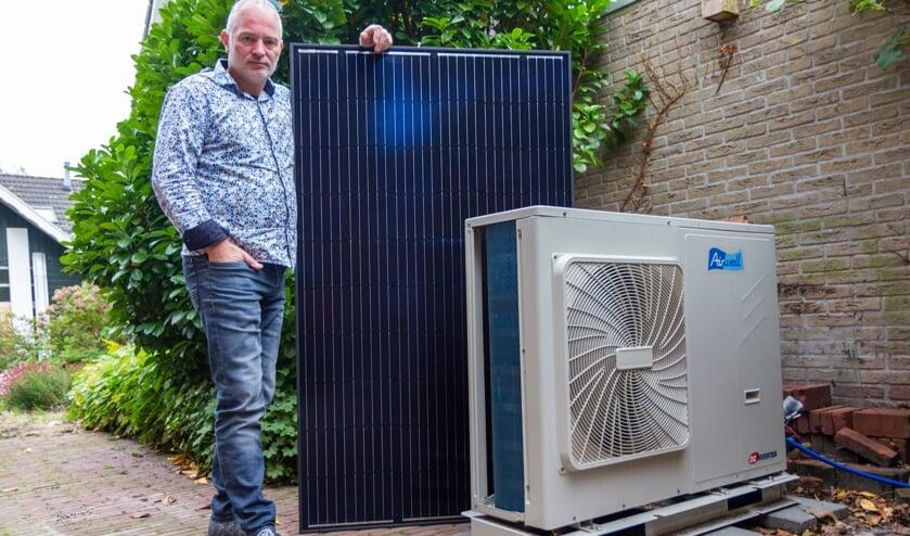 Jurgen Dijkstra bij de warmtepomp. Het losse zonnepaneel  gebruikt hij voor uitleg aan klanten.