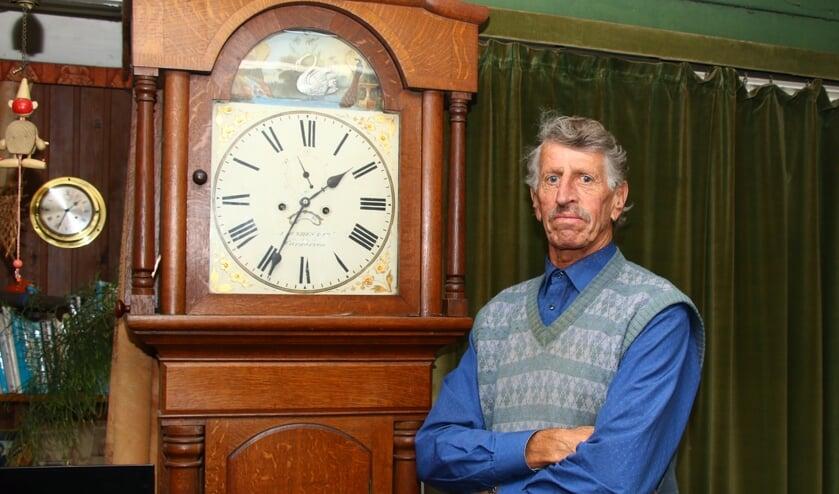 Lou Kuipers bij een klok in zijn woonkamer, boven de klokkenmakerij.