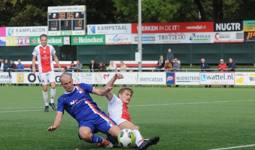Jorrit Terpstra van Buitenpost (blauw shirt) verwikkeld in een fel duel.