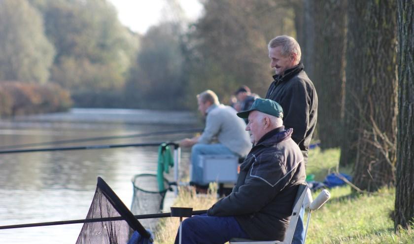 De hengelaars van 't Snoerke hebben zo nu en dan tijd voor een praatje, maar ze hebben vooral oog voor hun dobber en de vis die ze willen vangen.