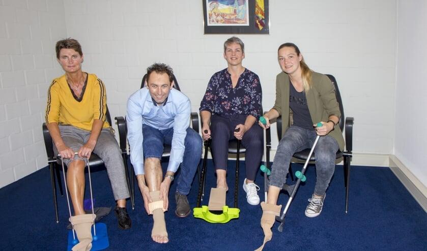 De compressietherapeuten Sjieuwke van der Bij, Klaas Helfrich, Jannie Vaatstra en Janet Spoelstra tonen vier verschillende aantrekhulpen.