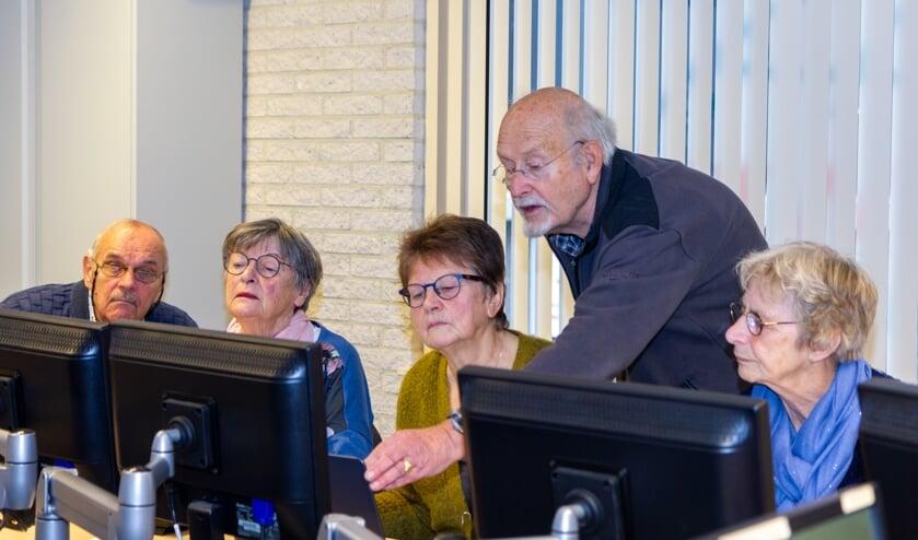 De vrijwilligers Fred Drost (uiterst links) en Pabe Wiersma tijdens een les over Windows 10.