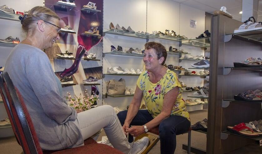 Aukje de Vries helpt een klant bij het vaststellen van de juiste schoenmaat.