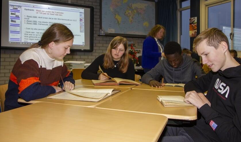 Lisa, Rebecca, Méthode en Mika bekijken tijdens de geschiedenisles archiefstukken van De Saad. De school bestaat 100 jaar. Vrijdag is er een ceremonie. Voor de leerlingen zijn er later dit jaar activiteiten. Bekijk de les met je app.