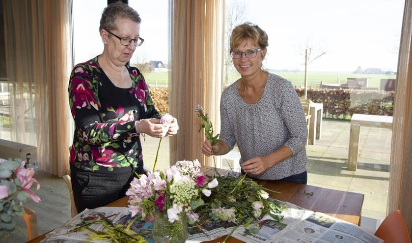 Een bewoner en medewerker van Herbergier Bartlehiem maken er een leuke middag van door samen te bloemschikken.