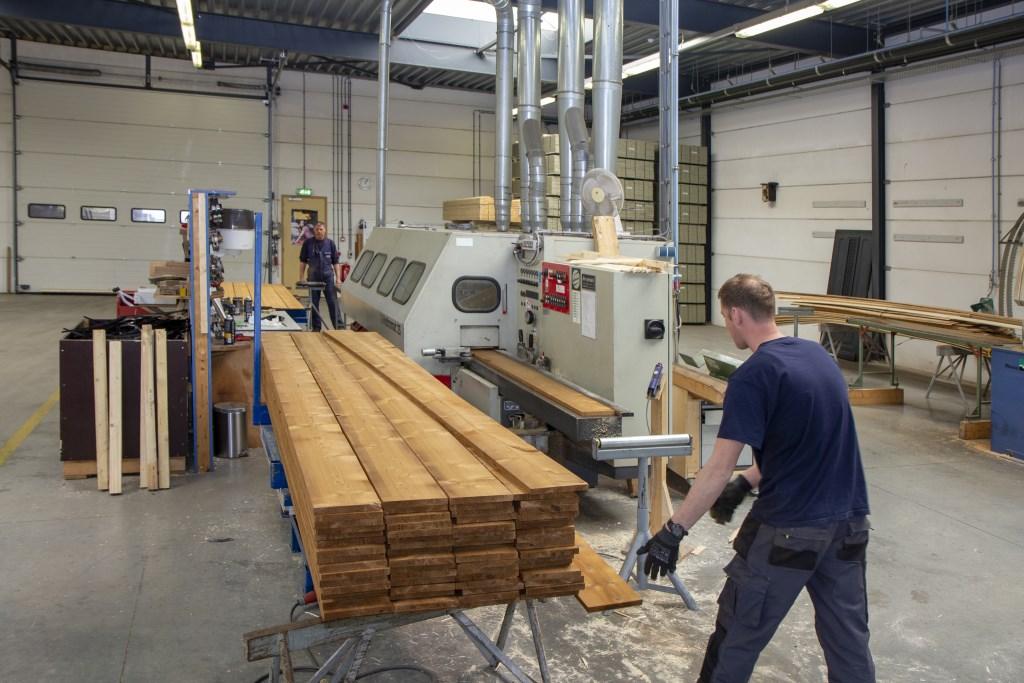 Jan Kroes en Arend Castelein schaven het hout in de werkplaats voor machinale houtbewerking tot planken met veer en groef. Foto: Actief Media © Actief Media