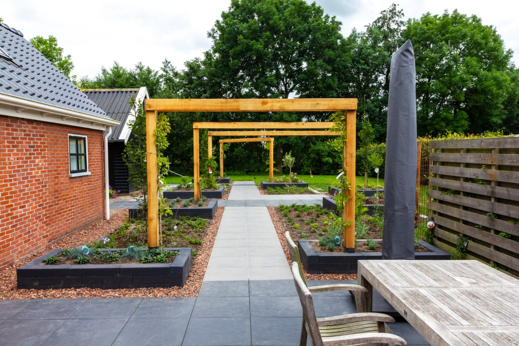 Een recent aangelegde tuin met veel strakke lijnen. De pergola's zorgen voor veel diepte. Foto: Actief Media