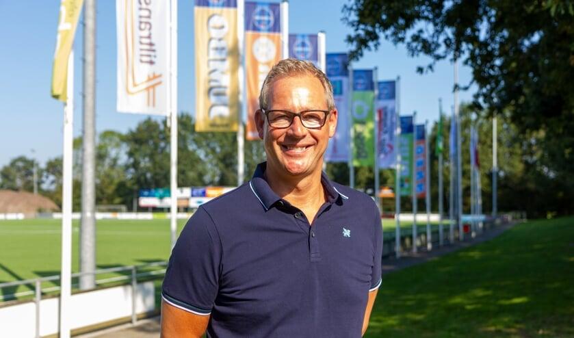Voorzitter Dirk van der Woude van FC Burgum voor de sponsorvlaggen met het nieuwe FC Burgum logo.