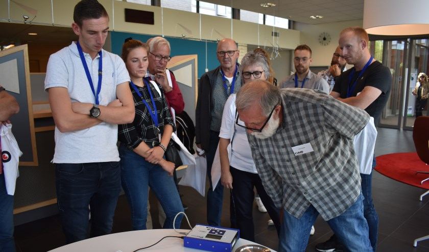 Gert Baatje (rechts voor) kijkt op een trillingsmeter en geeft er uitleg over.