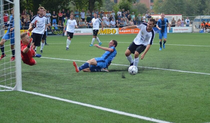 Aanvoerder Steffen Kempe van FC Burgum (blauw tenue) mist de bal net. Keeper Emile Peters is attent. Bekijk ook het filmpje via de Actief Plus-app.