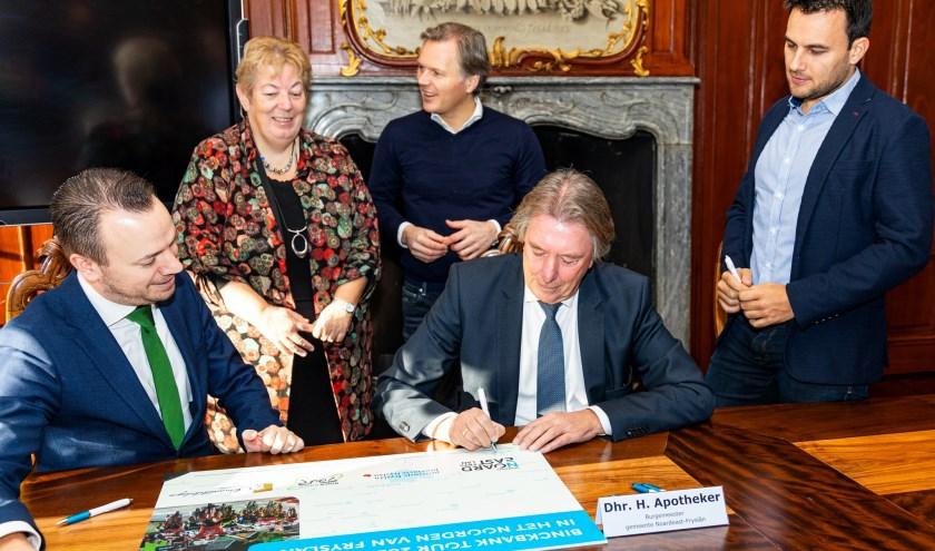 Burgemeester Apotheker tekent de overeenkomst in het bijzijn van  organisatoren en collega-bestuurders.