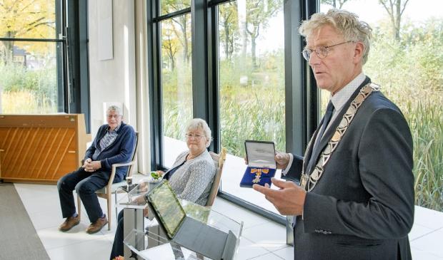 <p>Burgemeester Oebele Brouwer toont de onderscheiding die hij even later overhandigt aan het echtpaar Joop en Menke Land uit Surhuisterveen.&nbsp;</p>