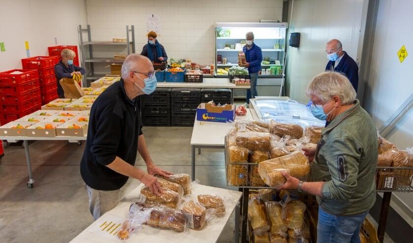<p>Vrijwilligers van de Voedselbank Drachten stellen de voedselpakketten samen.&nbsp;</p>
