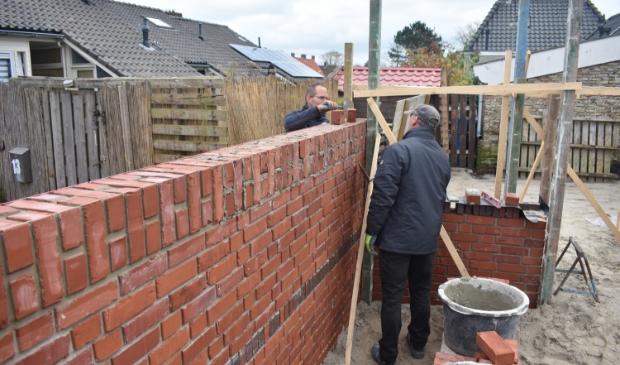 <p>Ale Annema (links) en Johannes Koree uit Anjum metselen de nieuwe muur in Hallum. Scan de foto met de ActiefPlus-app voor een kort interview met Dirk Vis en Sieta van der Woude.</p>