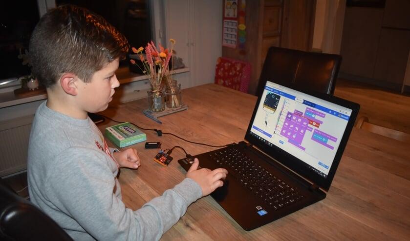 <p>Sven de Groot uit Dokkum programmeert met de microbit (bij zijn linker hand) en een laptop van z&#39;n ouders. Scan voor een filmpje de foto met de ActiefPlus-app.</p>