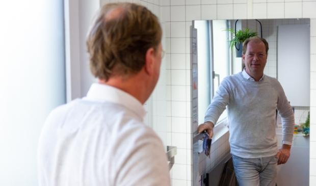 <p>Erik Meijer voor een infraroodpaneel dat is vormgegeven als een spiegel.</p>