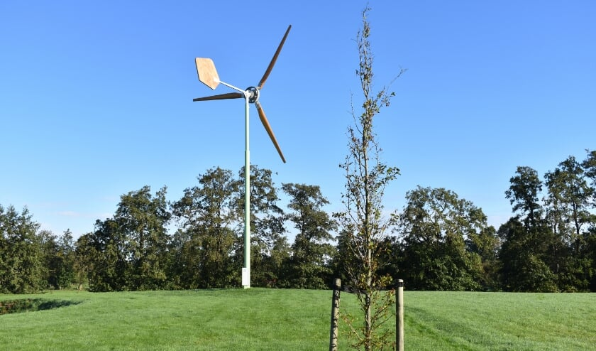 Een voorbeeld van een kleine windturbine, met houten wieken en windblad.