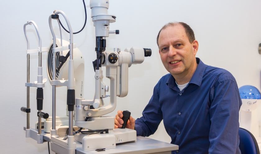 Theo Dijk bij een apparaat waarmee hij contactlenzen meet, maar ook staar kan vaststellen.