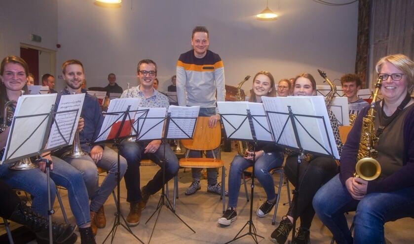 Dirigent Ido Kempenaar te midden van de orkestleden met wie hij zondag in Buitenpost een bijzonder evenement presenteert.