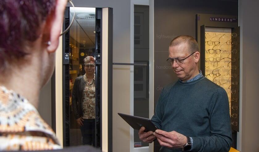 Jelle Brinksma geeft de klant instructies en bekijkt de  meetgegevens van de Visioffice X op de tablet.
