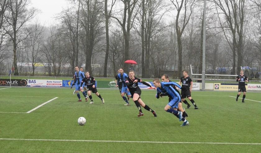 Harmen Vlietstra van FC Burgum (vooraan, blauw tenue) snelt langs een aantal tegenstanders van Be Quick Dokkum.