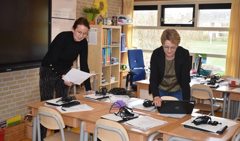 Fokje de Roos (links) en Thea van der Werff zetten de Chromebooks klaar voor leerlingen van groep 6 van 't Partoer.