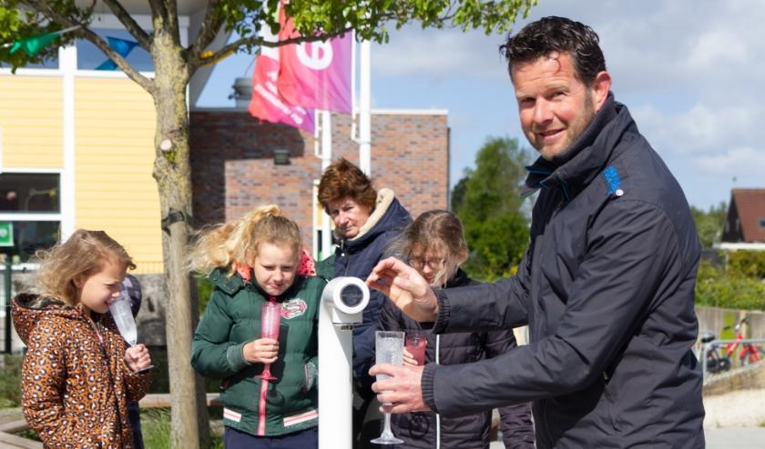 Schooldirecteur Nico Woudwijk tapt een glaasje vers water bij het nieuwe watertappunt.