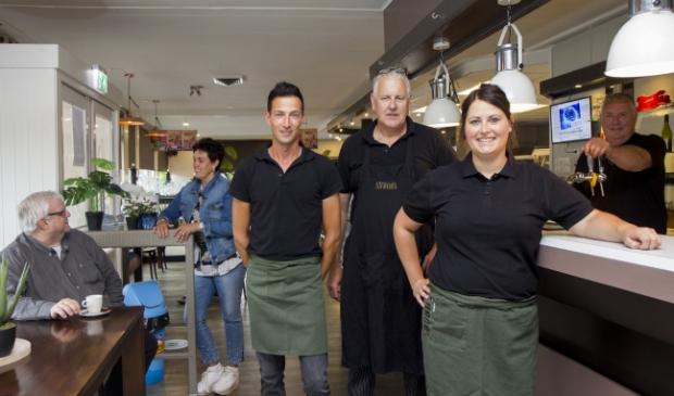 De keuken- en bedieningsmedewerkers van Sirenes in Drachten, van links naar rechts Gerrie de Boer, Louwe Nieuwenhuis en Iris Roufs. Op de achtergrond de ondernemers Gretha de Vries in gesprek met Nanne van der Veen van Apuls (zittend op de stoel) en Jan de Vries (achter de tap).