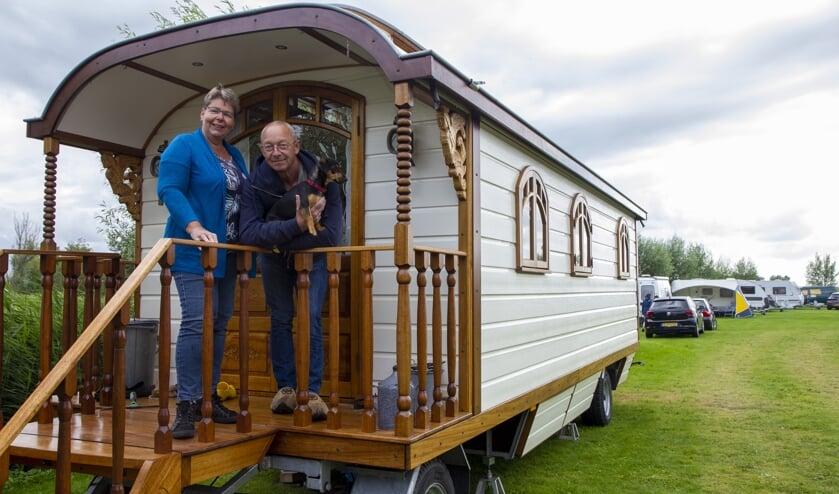 Jolanda en Ed Boonzaaijer op het bordes van hun zelfgebouwde pipowagen.