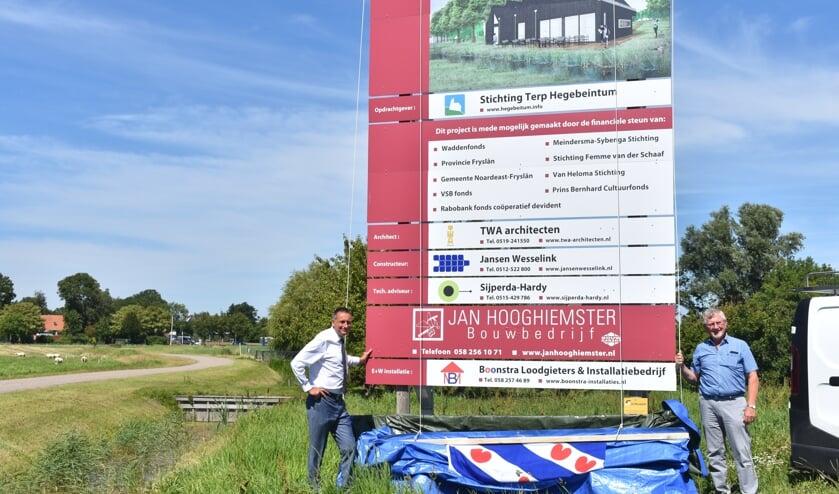 Wethouder Jelle Boerema (links) en secretaris Mient Holwerda onthullen het bouwbord voor het nieuwe bezoekerscentrum. De nieuwbouw begint na de bouwvak. Zie ook het filmpje met de Actief Plus-app.