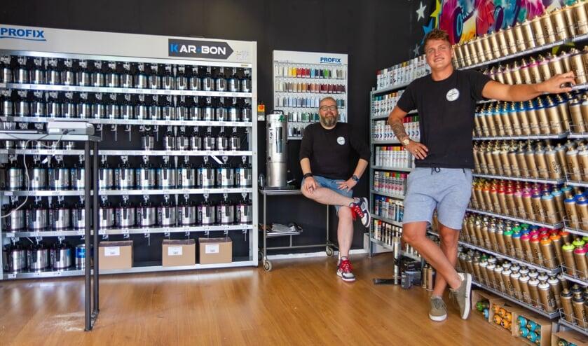 Gert Hamstra en Jens van der Sluis op de  nieuwe afdeling met linksachter de nieuwe autolakken en aan de rechterkant de graffitispuitbussen.