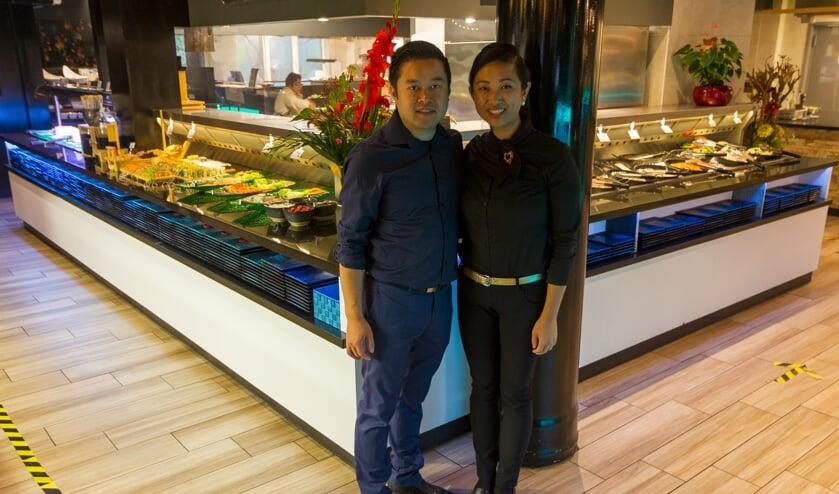 Sing-Long Hu en Chou Yun Bai voor het enorme buffet in het Golden Wok Paleis.