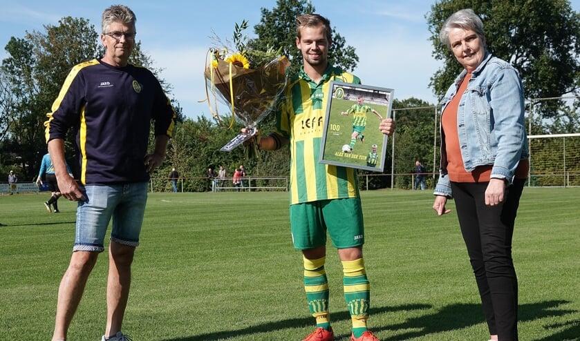 Jubilaris Alex van der Tuin krijgt een aandenken en bloemen van bestuursleden Jappie Borger en Coby Spinder.