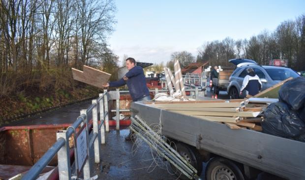Jan Spinder uit Drogeham gooit afvalhout weg. Op de achtergrond legen Fokko en Boukje Luchtenburg uit Augustinusga een aanhangwagen bouwafval.