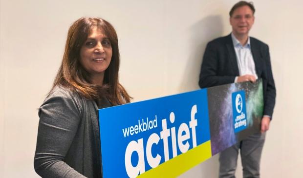 <p>De directieleden Shirley Bhagwat en Jan Auke Steegstra hangen het bord met het nieuwe<br>design van Weekblad Actief op. </p>