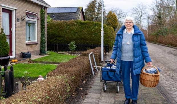 <p>Jos Holman, hier bij haar woning aan de Fjildwei 27 in Jistrum, legt haar zelfgebreide sokken geregeld in de bolderkar op zoek naar liefhebbers.</p>