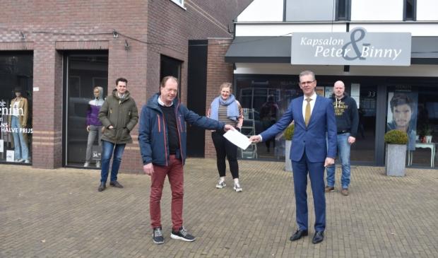 <p>Burgemeester Jeroen Gebben ontvangt van HIMBO-voorzitter Erik Meijer de oproep.<br>Andere HIMBO-bestuurders staan achter hen. Daarachter links Shoeby, dat niet<br>normaal open mag, rechts kapsalon Beter & Binny, die vanaf 3 maart wel open mag.</p>