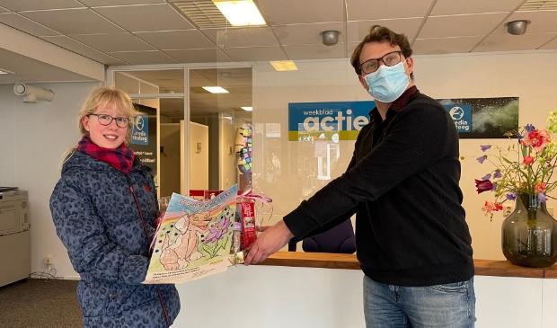 <p>Marrie Geke krijgt het bakpakket dat ze won overhandigd van redacteur Sytze Kobus.</p>
