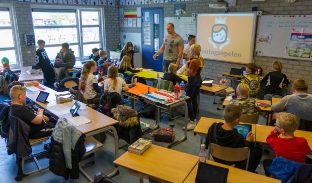 <p>De leerlingen van groep 7 zijn druk aan het werk. Leerkracht Willem Oostra geeft nu en dan aanwijzingen.</p>