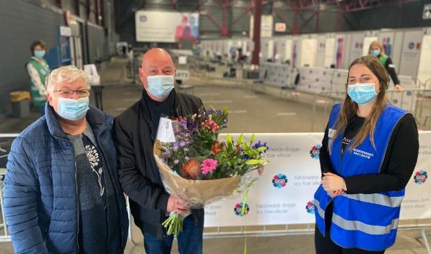 <p>GGD-medewerker Jantina Siegersma overhandigt de heer Dries van der Horst (73) uit Stiens een boeket bloemen. Met zijn vrouw kwam hij voor zijn eerste vaccinatieafspraak naar de Friese hoofdstad.</p>