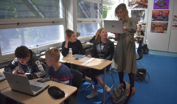 Docente Monique de Graaf helpt enkele leerlingen met de 'digitale escaperoom'.