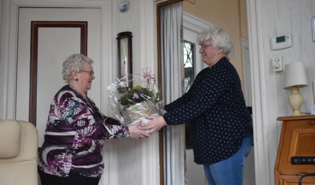 Jannie Smith (links) kreeg vrijdag al vast een plant uit handen van Alie Hofstra-Veenstra. Het officiële afscheidsfeestje moet wachten vanwege het coronavirus.