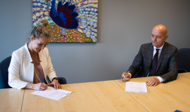 <p>Directeur Publieke Gezondheid, Margreet de Graaf van GGD Fryslân en Vincent Maas, voorzitter van de Raad van Bestuur van Zorggroep Alliade, ondertekenen het convenant.</p>