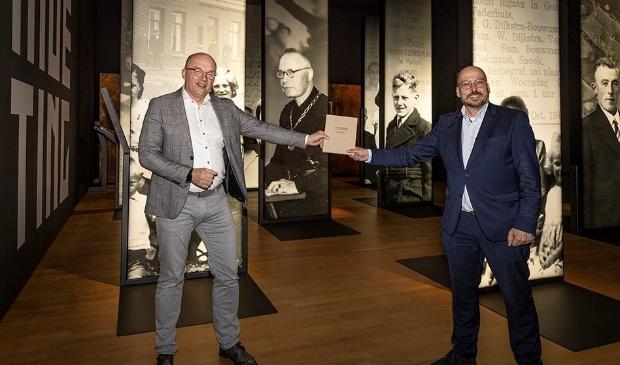 <p>Bestuurder Martin Kirchner van Noorderbreedte (links) overhandigt het boek aan Kris Callens, in het Fries Verzetsmuseum.</p>