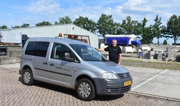 Marco den Dulk op het terrein van gemeentewerken bij 'zijn' auto.